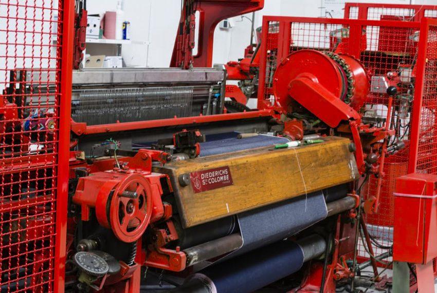 Aperçu d'une machine historique industrielle, un métier à tissr rouge et bois pour la confection du tissu.
